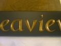 House sign hand carved out of Welsh slate, painted gold and oiled.