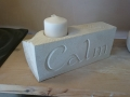 Pillar candle holder with flower leaves and calm carved into it. Portland limestone.