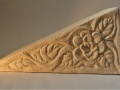 triangle carved with a rose and leaves.